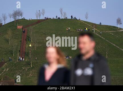 Dortmund, Germany. 28th Mar, 2020. In the afternoon, walkers are out on the promenade of Lake Phoenix and the adjacent slagheap in spring weather. To contain the coronavirus, NRW has banned all accumulations of three or more people in public. Credit: Bernd Thissen/dpa/Alamy Live News Credit: dpa picture alliance/Alamy Live News Credit: dpa picture alliance/Alamy Live News - Stock Photo