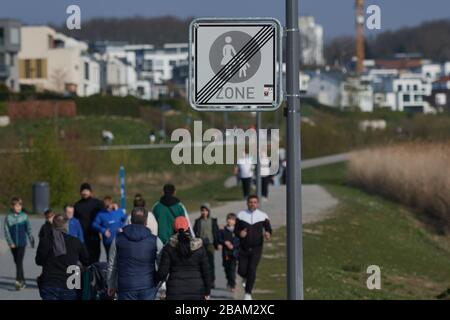 Dortmund, Germany. 28th Mar, 2020. In the afternoon, walkers walk along the promenade of the Phoenix Lake in springlike weather. To contain the coronavirus, NRW has banned all gatherings of three or more people in public. Credit: Bernd Thissen/dpa/Alamy Live News Credit: dpa picture alliance/Alamy Live News Credit: dpa picture alliance/Alamy Live News - Stock Photo