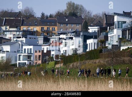 Dortmund, Germany. 28th Mar, 2020. In the afternoon, walkers are out on the shores of Lake Phoenix in spring-like weather. To contain the coronavirus, NRW has banned all accumulations of three or more people in public. Credit: Bernd Thissen/dpa/Alamy Live News Credit: dpa picture alliance/Alamy Live News Credit: dpa picture alliance/Alamy Live News - Stock Photo