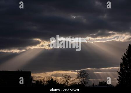 London, UK. 28th March 2020. After a week of fine weather with blue skies heavy cloud moves into the south east of England bringing unsettled weather. Crepuscular rays, shafts of sunlight, pierce through breaks in the cloud layer mid evening. Credit: Malcolm Park/Alamy Live News. - Stock Photo
