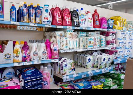 Variety washing-powders, baby diapers and toilet paper on supermarket shelf.