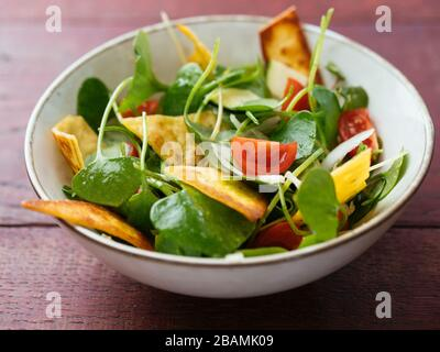 Winter purslane salad with zucchini, tomatoes, onions and toasted tortillas. - Stock Photo