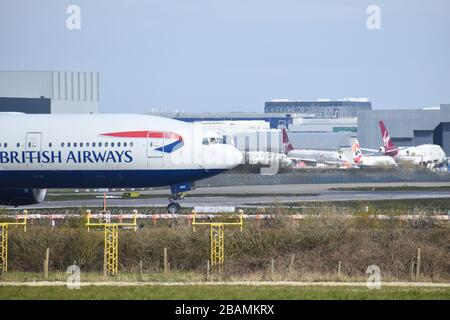A British Airways Boeing 777-236 moves towards the runway for takeoff at Gatwick Airport, passing in front of some grounded Virgin aircraft.
