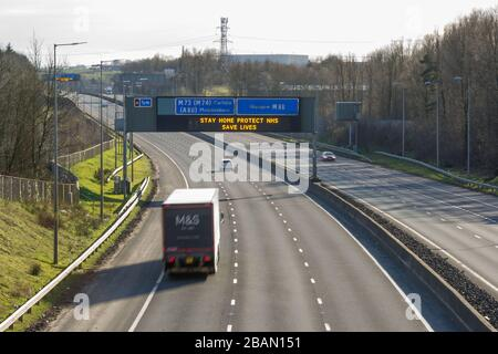 """Glasgow, UK. 28th Mar, 2020. Pictured: Road signs all along the M8 and M80 motorways which read, """"STAY HOME PROTECT NHS SAVE LIVES"""" The Coronavirus Pandemic has forced the UK Government to order a shut down of all the UK major cities and make people stay at home, which has left the motorways and all other roads free of the usual nose to tail traffic which would otherwise be there. Credit: Colin Fisher/Alamy Live News - Stock Photo"""