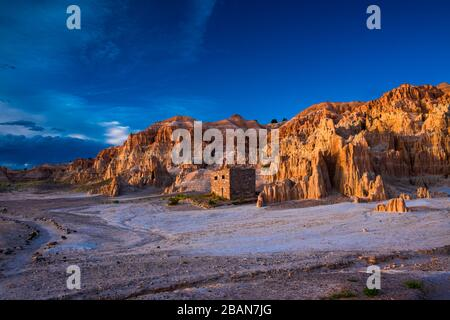 Golden light paints the hills of the picnic area of Cathedral Gorge as the sun sets - Stock Photo