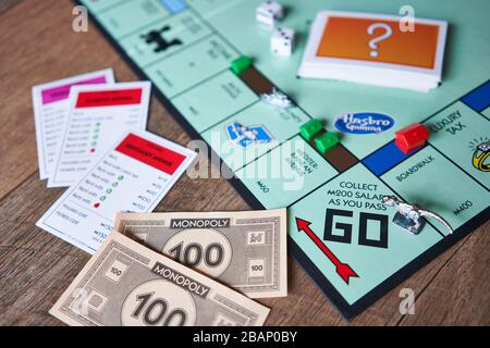 Closeup of Monopoly board game isolated on a wooden background. The classic fast-dealing property trading board game is currently published by Hasbro. - Stock Photo