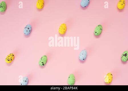 Multi-colored quail eggs on a pink background. Yellow, blue and green little easter eggs. Seamless pattern. - Stock Photo