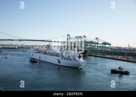Los Angeles, USA. 27th Mar, 2020. The Military Sealift Command hospital ship USNS Mercy (T-AH 19) arrives in Los Angeles, Calif., March 27, 2020. Mercy deployed in support of the nationÕs COVID-19 response efforts, and will serve as a referral hospital for non-COVID-19 patients currently admitted to shore-based hospitals. This allows shore base hospitals to focus their efforts on COVID-19 cases. One of the Department of DefenseÕs missions is Defense Support of Civil Authorities. DOD is supporting the Federal Emergency Management Agency, the lead federal agency, as well as state, local and publ - Stock Photo