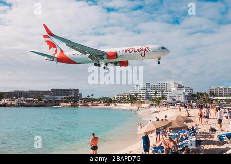 An Air Canada Rouge Boeing 767 comes in to land over tourists on Maho Beach, St. Maarten - Stock Photo