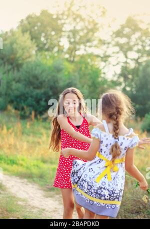 Two Happy cute  little girls having fun and dancing at sunny summer day outdoors - Stock Photo