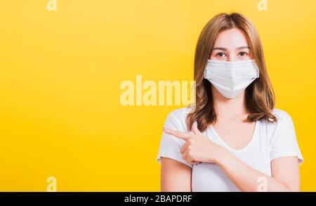Portrait Asian beautiful young woman wearing face mask protects filter dust pm2.5 anti-pollution, anti-smog, air pollution and COVID virus her pointin - Stock Photo
