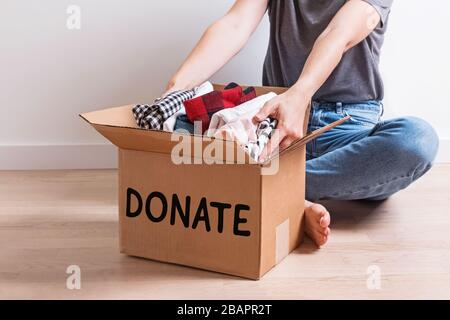 Woman putting her clothes in a carboad box with text Donate written on it. - Stock Photo