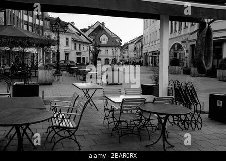 Kranj, Slovenia, March 20, 2020: Empty tables of closed bars and restaurants in the old city center of Kranj, Slovenia, during the coronavirus outbreak nationwide lockdown. - Stock Photo