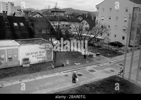 Kranj, Slovenia, March 22, 2020: Two elderly women speak to each other on the street maintaining a large distance in accordance with social distancing rules during the coronavirus outbreak nationwide lockdown. - Stock Photo