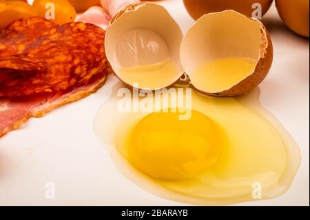 Broken chicken egg and slices of bacon and sausage on a white background. Close up - Stock Photo