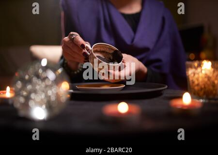 Close-up of woman fortuneteller's hands divining on coffee grounds at table with predictive ball in room