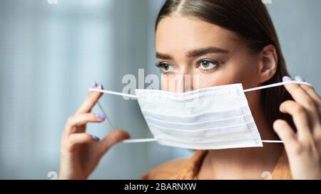 Portrait of woman in quarantine wearing medical mask - Stock Photo