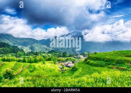 Clouds hanging over the Yunhe cloud rice terraces landscape in the summer in Zhejiang province China. - Stock Photo