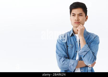 Portrait of skeptical man thinking, making choice facing decision and being displeased with it, smirk disappointed looking away while pondering someth - Stock Photo