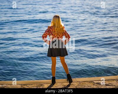 Rearview rear-view  young woman near sea standing looking away in distance hands on hips striking pose posing - Stock Photo