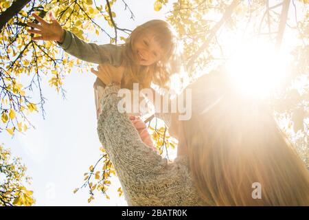 Closeup of beautiful young mother holding her little cheerful daughter in hands while having fun outdoors. Mom and her young child playing in autumn p