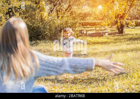 Nice little girl running into her mother's hug and smiling. Daughter laughing and running towards mother's hands to embrace on nature. Mom and child h - Stock Photo