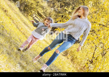 Beautiful woman holding hand of her little daughter and smiling while running together in autumn park. Tiny girl playing and having fun with her young - Stock Photo