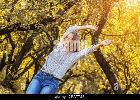 Cheerful young woman rotating around, spinning and having fun in autumn park. Beautiful hipster girl in cozy wear in motion holding hands up and laugh