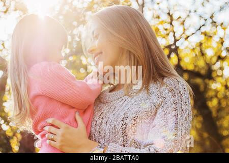Closeup of happy young family spending time together outdoors. Young mother holding her little daughter in hands and hugging her while standing in aut