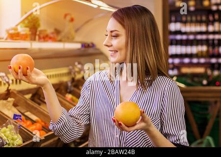 Portrait of beautiful girl holding oranges or tangerines in hands and smiling while standing at fruit market. Young cheerful woman doing shopping at b - Stock Photo