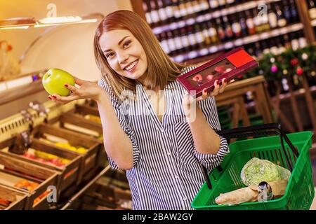 Cheerful young woman holding apple in one hand and chocolate bar in another and smiling while doing shopping at grocery supermarket. Hard choice betwe - Stock Photo