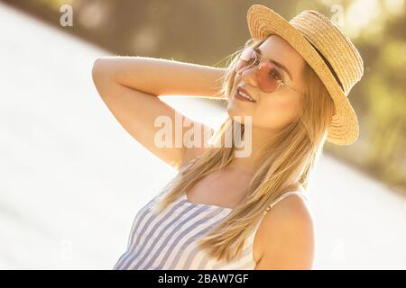 Portrait of tender young woman in straw hat and sunglasses standing at sunny riverside. Beautiful stylish girl in stripped overalls posing at beach on - Stock Photo