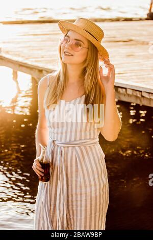 Portrait of happy young woman in straw hat and stripped overalls holding bottle of lemonade in hand while standing at riverside. Beautiful blonde girl - Stock Photo
