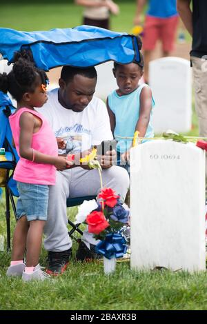 'Terrail Blair, center, and his daughters Teyyuana, 6, right, and Takiyah, 5, left, visit the grave of his brother U.S. Navy Petty Officer 2nd Class Mark Mayo in Section 60 of Arlington National Cemetery for Memorial Day, May 30, 2016, in Arlington, Va. Mayo was killed March 24, 2014, while on patrol at Norfolk Naval Station. (U.S. Army photo by Rachel Larue/Arlington National Cemetery/released); 30 May 2016, 12:45; Memorial Day in Arlington National Cemetery; Arlington National Cemetery; ' - Stock Photo