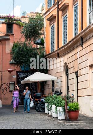 Two women walking down a side street in Trastevere, Rome, Lazio, Italy, Europe, color