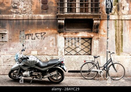 A motorcycle, bicycle and anti-semitic graffiti on a side street in Rome, Lazio, Italy, Europe, color