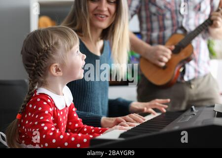 Parents teach daughter to play musical instruments Stock Photo