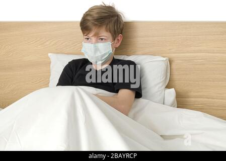 boy in antivirus mask sits on quarantined bed after travel - Stock Photo