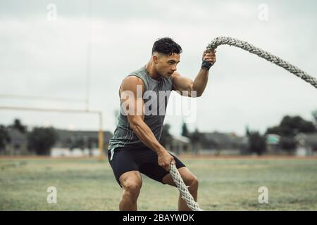 Strong man exercising with battle ropes. Athlete doing battle rope workout outdoors on a field. - Stock Photo