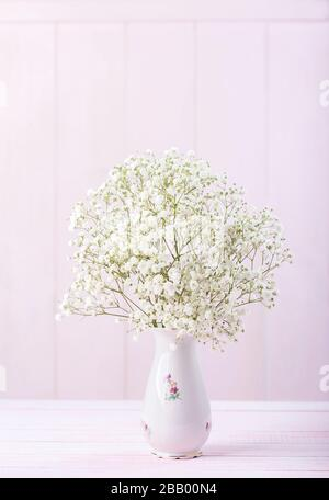 Small bouquet of Gypsophila flowers in porcelain vase against a light pink wooden background. Selective focus.