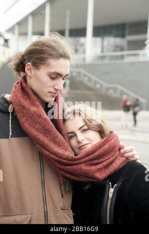 young couple sharing winter scarf - Stock Photo