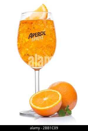LONDON, UK - APRIL 01, 2020: Aperol Spritz summer cocktail with ice and orange slice in wine glass on white background with fresh oranges and mint lea - Stock Photo