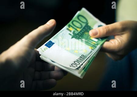 Close-up Of Person Hand Giving Money To Other Hand. Transfer of Euro Banknotes.