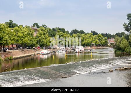 Weir and tourist sightseeing boats on the river Dee, Chester, Cheshire, England, UK - Stock Photo
