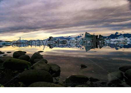 Sunrise over Jokulsarlon glacier lagoon, mirror like water filled with icebergs, Iceland. - Stock Photo