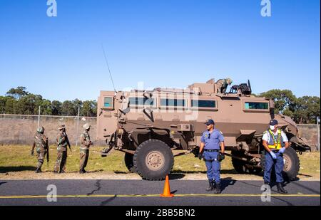 Cape Town, South Africa. 30th Mar, 2020. a members of the South African Police Service (SAPS) and the South African National Defence Force (SANDF) stand guard at a roadblock on the N2 near Khayelitsha after the South African government declared a 21 day COVID-19 lockdown as part of the State of National Disaster declaration by President Cyril Ramaphosa. The Health Ministry has asked residents to observe the regulations, practise hygiene, stay at home and practise social distancing. Credit: Roger Sedres/Alamy Live News - Stock Photo
