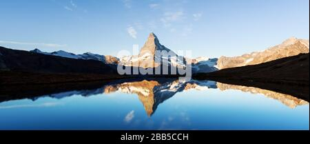 Picturesque landscape with colorful sunrise on Stellisee lake. Snowy Matterhorn Cervino peak with reflection in clear water. Zermatt, Swiss Alps - Stock Photo