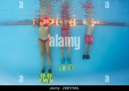 Happy family has fun, relax at poolside after swimming lesson. Underwater photo of people group in pool. Healthy lifestyle, active parents - Stock Photo