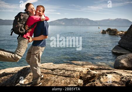 Mid-adult woman excitedly hugging her boyfriend next to beautiful lake. - Stock Photo