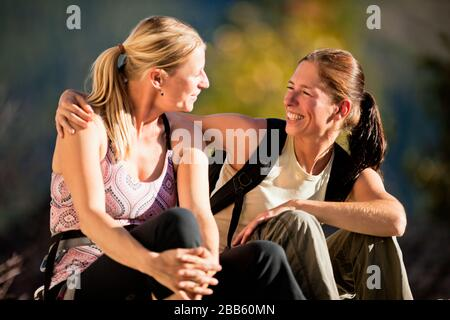 Two rock-climbing friends sitting and talking on the mountain top. - Stock Photo